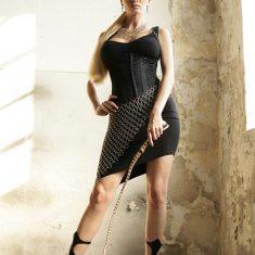 Femme autoritaire en mini jupe et fouet